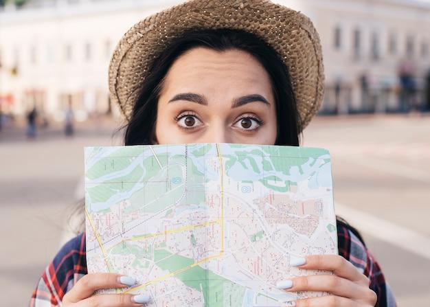 Zdziwiona młoda kobieta jest ubranym kapeluszowego nakrycie jej usta z mapą przy outdoors