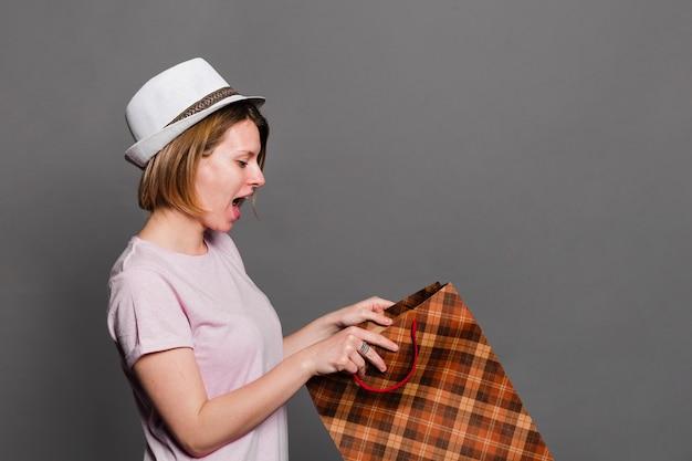 Zdziwiona młoda kobieta jest ubranym kapeluszowy patrzeć wśrodku torba na zakupy
