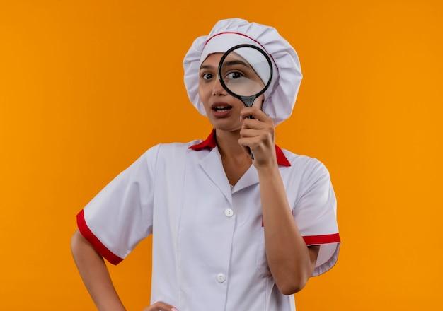 Zdziwiona młoda kobieta kucharz ubrana w mundur szefa kuchni patrząc na kamery przez lupę na na białym tle pomarańczowy