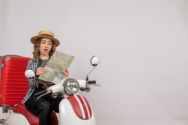 Zdziwiona młoda kobieta na motorowerze patrząca na mapę na szaro