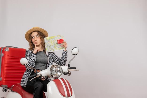 Zdziwiona młoda kobieta na motorowerze trzymająca kartę i mapę na szaro