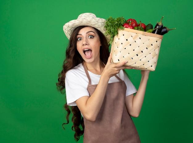 Zdziwiona młoda kobieta ogrodniczka w mundurze na sobie kapelusz ogrodniczy trzyma kosz warzyw na zielonej ścianie z miejsca na kopię
