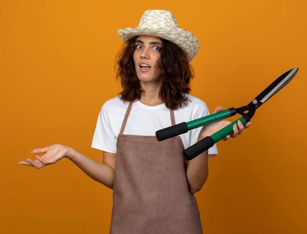 Zdziwiona młoda kobieta ogrodniczka w mundurze na sobie kapelusz ogrodniczy, trzymając maszynkę do strzyżenia i rozkładając rękę