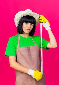 Zdziwiona młoda kobieta ogrodnik w mundurze na sobie kapelusz ogrodniczy trzyma centymetr na białym tle na różowym tle z miejsca na kopię