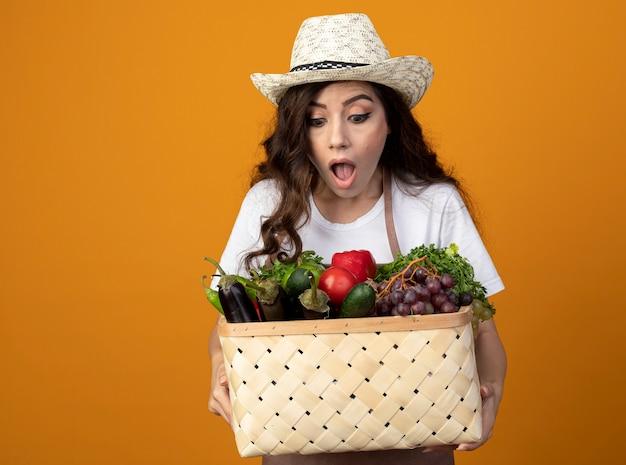 Zdziwiona młoda kobieta ogrodnik w mundurze na sobie kapelusz ogrodniczy trzyma i patrzy na kosz warzyw na pomarańczowej ścianie z miejsca na kopię