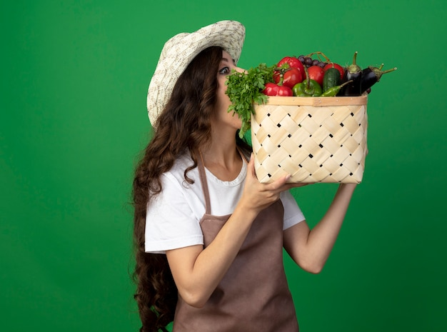 Zdziwiona młoda kobieta ogrodnik w mundurze na sobie kapelusz ogrodniczy trzyma i patrzy na kosz warzyw na zielonej ścianie z miejsca na kopię