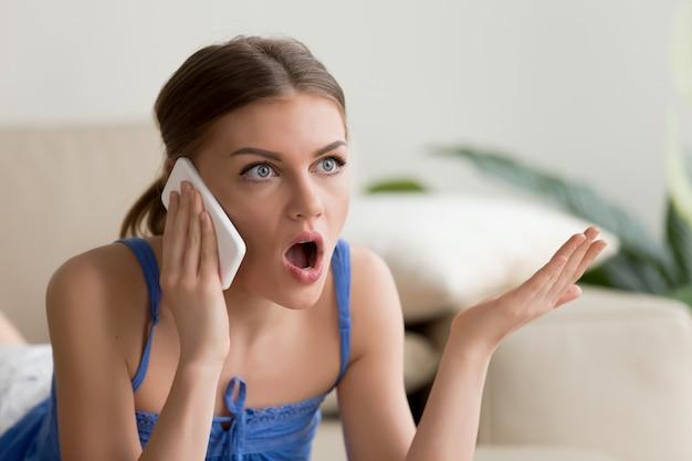 Zdziwiona młoda kobieta opowiada na telefonie komórkowym