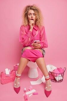 Zdziwiona młoda kobieta opuszcza ważne spotkanie z powodu biegunki patrzy zszokowana trzyma telefon czeka na telefon w eleganckim ubraniu siedzi na muszli klozetowej przy różowej ścianie. zaparcie