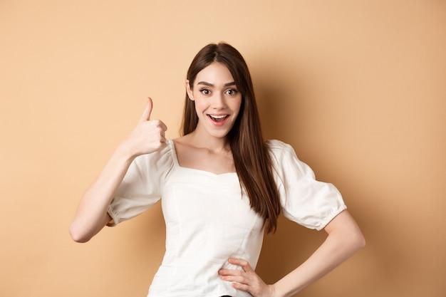 Zdziwiona młoda kobieta pokazująca kciuk do góry, mówi tak i chwal świetny produkt, zatwierdza wybór, stojąc zadowolona na beżowym tle.