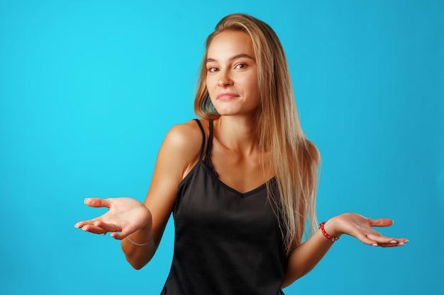 Zdziwiona młoda kobieta pokazująca, że nie wie.
