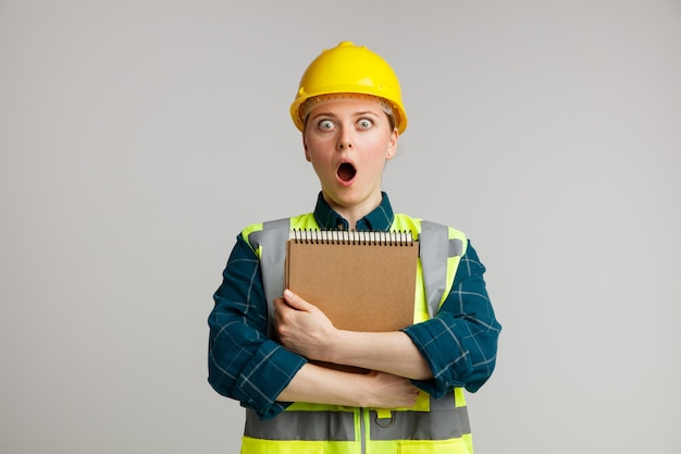 Zdziwiona młoda kobieta pracownik budowlany w kasku ochronnym i przytulanie notatnika kamizelka odblaskowa