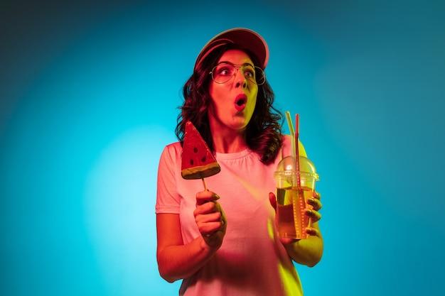 Zdziwiona młoda kobieta stojąca z napojem i słodyczami nad modnym niebieskim neonem