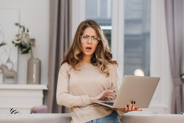 Zdziwiona młoda kobieta trzyma laptopa w beżowym stroju