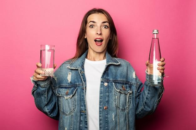 Zdziwiona młoda kobieta trzyma szklankę z wodą i szklaną butelką wody na różowej powierzchni