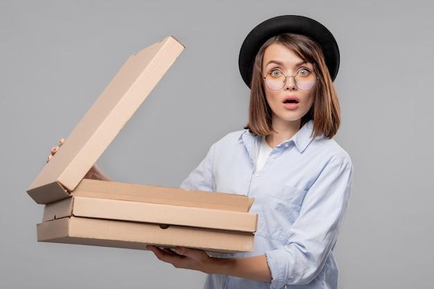 Zdziwiona młoda kobieta w codziennym stroju, otwierająca jeden z pudełek kartonowych