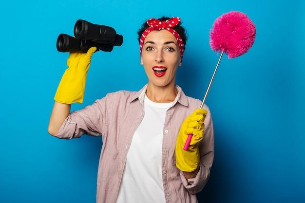 Zdziwiona młoda kobieta w czyszczących rękawiczkach, trzymając lornetkę i szczotka do kurzu na niebieskiej powierzchni