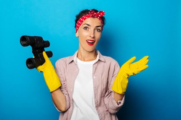 Zdziwiona młoda kobieta w czyszczących rękawiczkach trzymając lornetkę na niebieskiej powierzchni