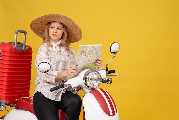 Zdziwiona młoda kobieta w kapeluszu i siedzi na motocyklu i trzymając mapę na żółto