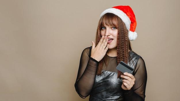 Zdziwiona młoda kobieta w kapeluszu świętego mikołaja trzyma kartę kredytową lub debetową. miejsce na kopię. baner internetowy.