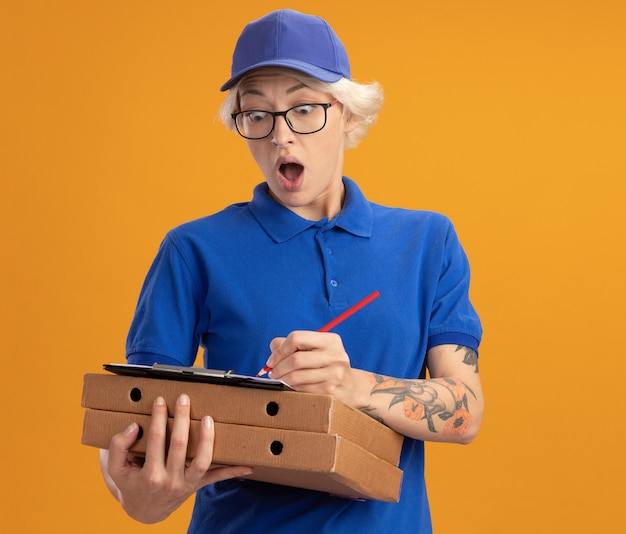 Zdziwiona młoda kobieta w niebieskim mundurze i czapce w okularach trzymająca pudełka po pizzy i schowek z pustymi stronami pisząca coś ołówkiem na pomarańczowej ścianie
