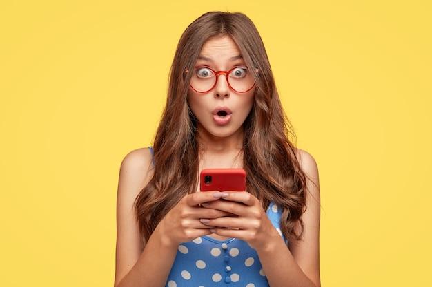 Zdziwiona młoda kobieta w okularach, pozowanie na żółtej ścianie