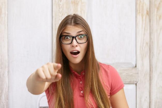 Zdziwiona młoda kobieta w prostokątnych okularach i koszulce polo wskazująca palcem wskazującym z przodu