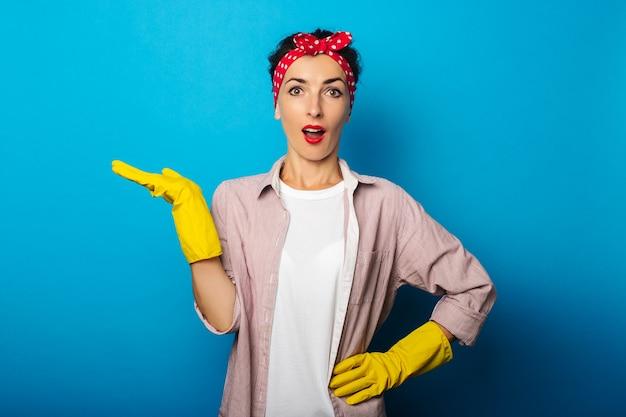 Zdziwiona młoda kobieta w rękawiczkach trzyma niewidzialny obiekt pokazując kciuk w górę gest na niebieskiej powierzchni