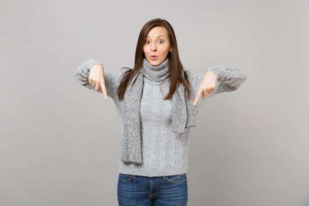 Zdziwiona młoda kobieta w szary sweter szalik wskazując palcem w dół na białym tle na szarym tle w studio. zdrowy styl życia moda, szczere emocje ludzi, koncepcja zimnej pory roku. makieta miejsca na kopię.