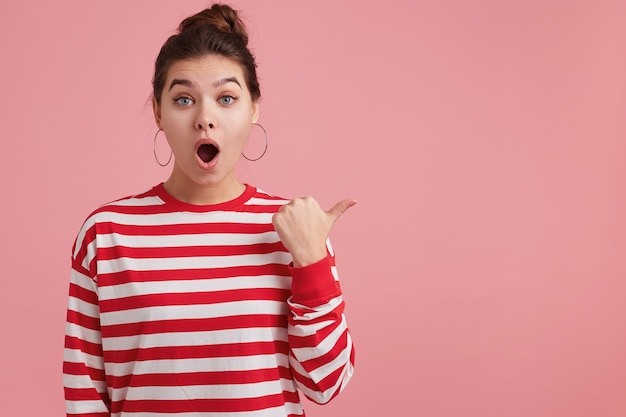 Zdziwiona młoda kobieta z piegami, nosi longsleeve w paski; szeroko otwiera usta z podniecenia, opadająca szczęka, przyciąga uwagę, odizolowane na różowych punktach ściany z kciukiem po prawej stronie w przestrzeni kopii.
