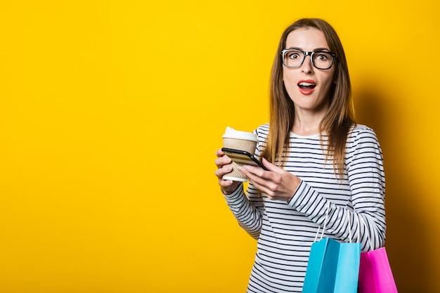 Zdziwiona młoda kobieta z telefonem, z torby na zakupy, na żółtym tle