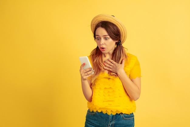 Zdziwiona młoda kobieta za pomocą smartfona