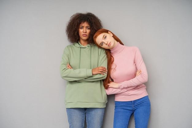 Zdziwiona młoda, ładna brązowowłosa ciemnoskóra kobieta z założonymi rękami i smutnym spojrzeniem, pozując na szarej ścianie ze swoim spokojnym przyjacielem rudej