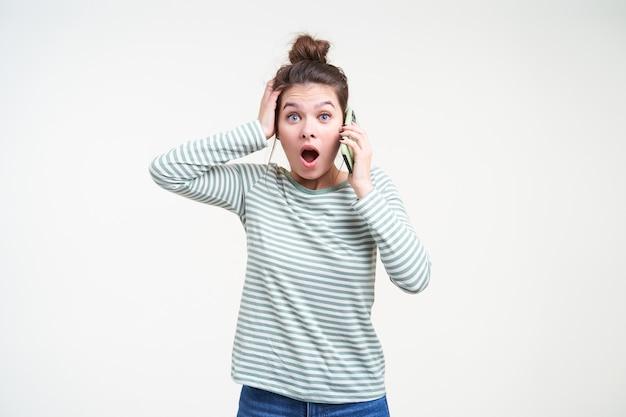 Zdziwiona młoda ładna brązowowłosa kobieta z przypadkową fryzurą, trzymając podniesioną dłoń na głowie, patrząc oszołomiony z przodu, stojącą nad białą ścianą z telefonem komórkowym w uniesionej ręce