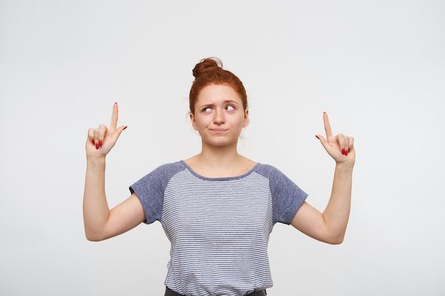Zdziwiona młoda, ładna ruda kobieta z swobodną fryzurą, trzymając usta złożone i unoszącą brwi, pokazując w górę palcami wskazującymi, odizolowaną na białej ścianie