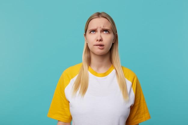 Zdziwiona młoda niebieskooka blond kobieta o długich włosach marszczy brwi i patrzy w zamyśleniu w górę, stojąc na niebieskim tle z opuszczonymi rękami