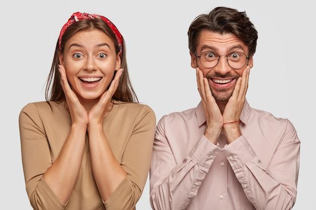 Zdziwiona młoda para pozuje przy białej ścianie
