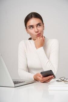 Zdziwiona młoda piękna brunetka kobieta z fryzurą w kucyk wykręcająca usta, patrząc w zadumie w górę, opierająca brodę na uniesionej dłoni, odizolowana na białej ścianie