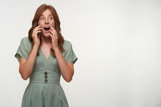 Zdziwiona młoda piękna kobieta o rudych włosach pozuje, szeroko otwiera usta i zakrywa je ręką, trzymając smartfon przy uchu