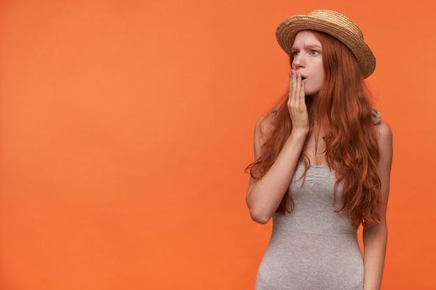 Zdziwiona młoda piękna, lisia długowłosa kobieta patrząca na bok z dłonią na ustach, marszcząca brwi z zaskoczonymi otwartymi ustami, pozująca na pomarańczowym tle w zwykłych ubraniach