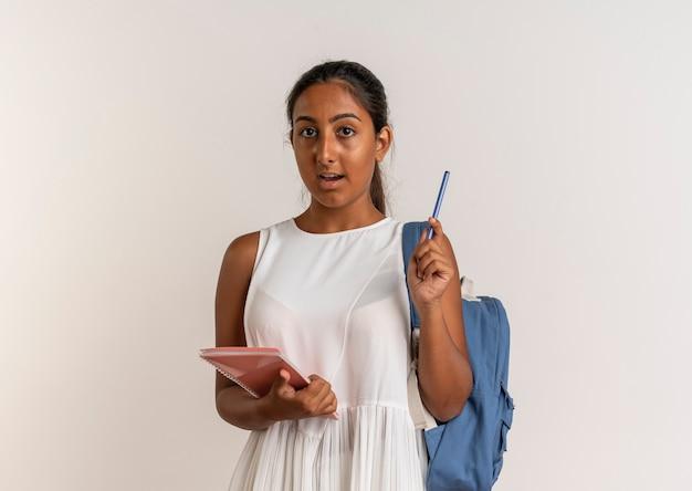 Zdziwiona młoda uczennica na sobie tylną torbę trzymając notatnik i długopis na białym tle