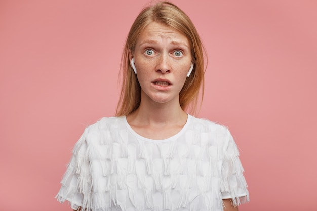 Zdziwiona młoda, urocza dama z lśniącymi włosami marszczącymi się na czole, patrząc zdezorientowana w kamerę i pokazująca zęby, ubrana w eleganckie ubrania, pozując na różowym tle