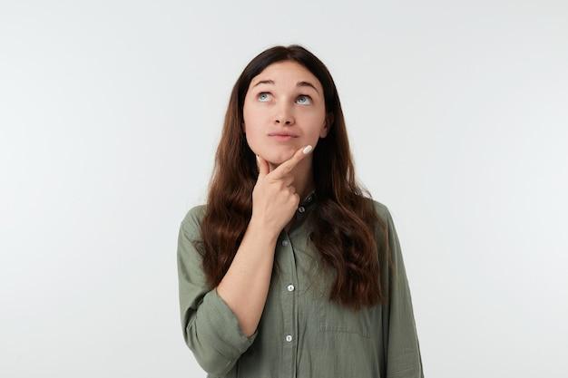 Zdziwiona młoda urocza długowłosa dama z naturalnym makijażem trzymająca uniesioną dłoń na brodzie