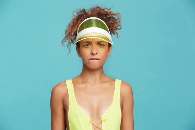 Zdziwiona młoda zielonooka rudowłosa kręcona dama marszczy brwi i gryzie skręcone usta patrząc w kamerę, stojąc na niebieskim tle z opuszczonymi rękami