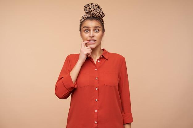 Zdziwiona młoda zielonooka urocza brunetka kobieta trzyma palec wskazujący na dolnej wardze, patrząc zmieszanym z przodu, stojąc nad beżową ścianą