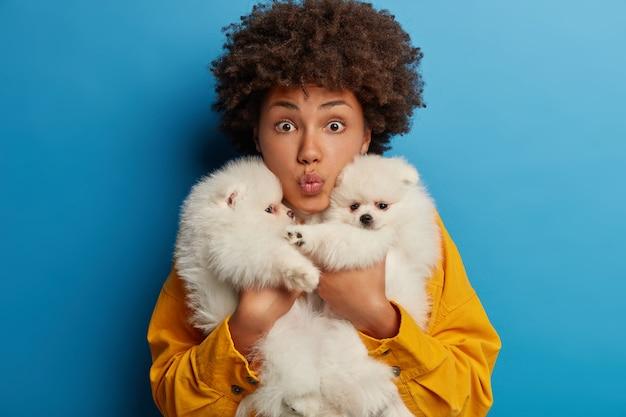 Zdziwiona nastolatka nosi dwa rodowodowe szczenięta, odpoczywa razem po wizycie u weterynarza i spacerze, nie wyobraża sobie życia bez psów