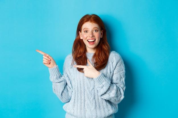 Zdziwiona nastolatka o rudych włosach i piegach, wskazująca palcem w lewo i uśmiechnięta, pokazująca reklamę, stojąca na niebieskim tle.
