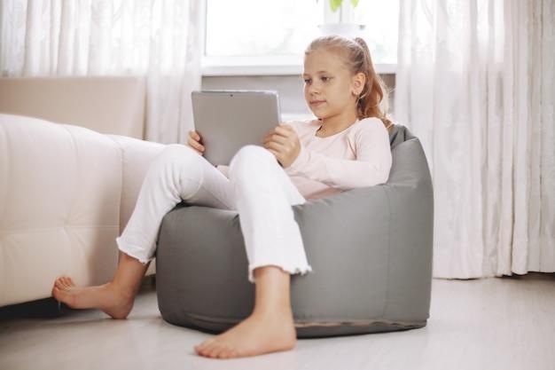Zdziwiona nastolatka siedzi w fotelu worek fasoli w białym pokoju, odrabia lekcje z tabletem