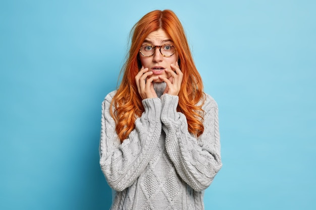 Zdziwiona, nerwowa kobieta z długimi rudymi włosami trzyma ręce na twarzy z zaniepokojonym wyrazem, boi się mówienia ma zakłopotany wygląd i reakcję na coś, co nosi sweter z dzianiny.