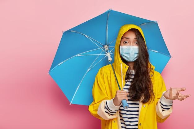 Zdziwiona, nerwowa koreanka podnosi dłoń z oburzeniem, nosi maskę ochronną i płaszcz przeciwdeszczowy