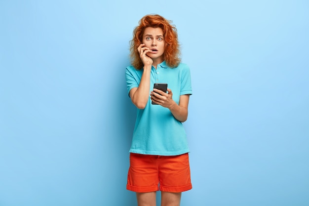 Zdziwiona niezadowolona rudowłosa kobieta, zszokowana, że nie otrzymała potwierdzenia e-mail, trzyma nowoczesny telefon komórkowy